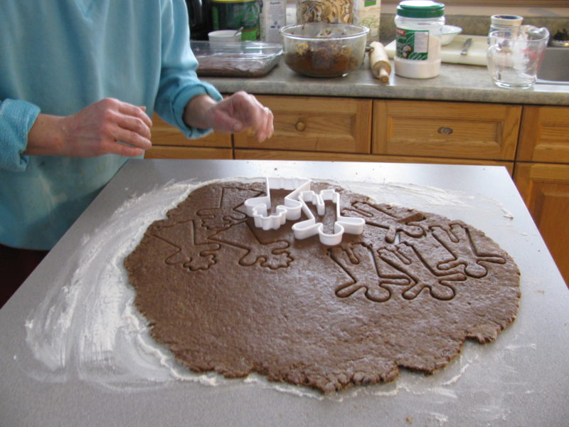 Using cookie cutters to make Gingerbread Boys.