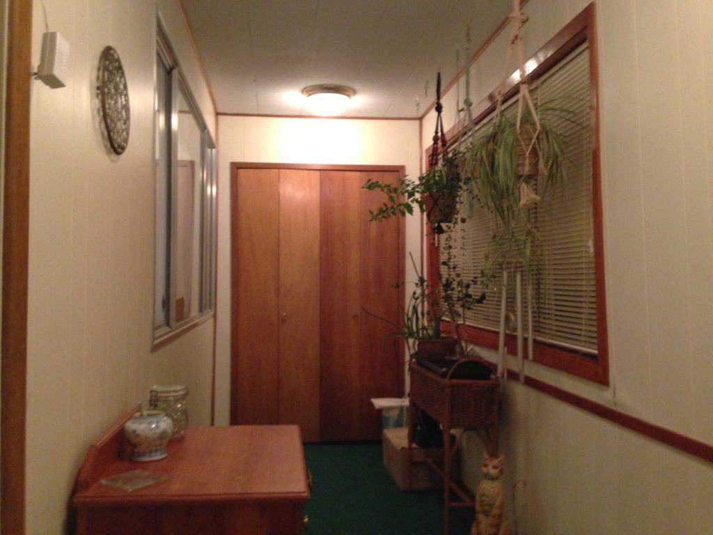 After photo of mud room with bright paint over paneling.