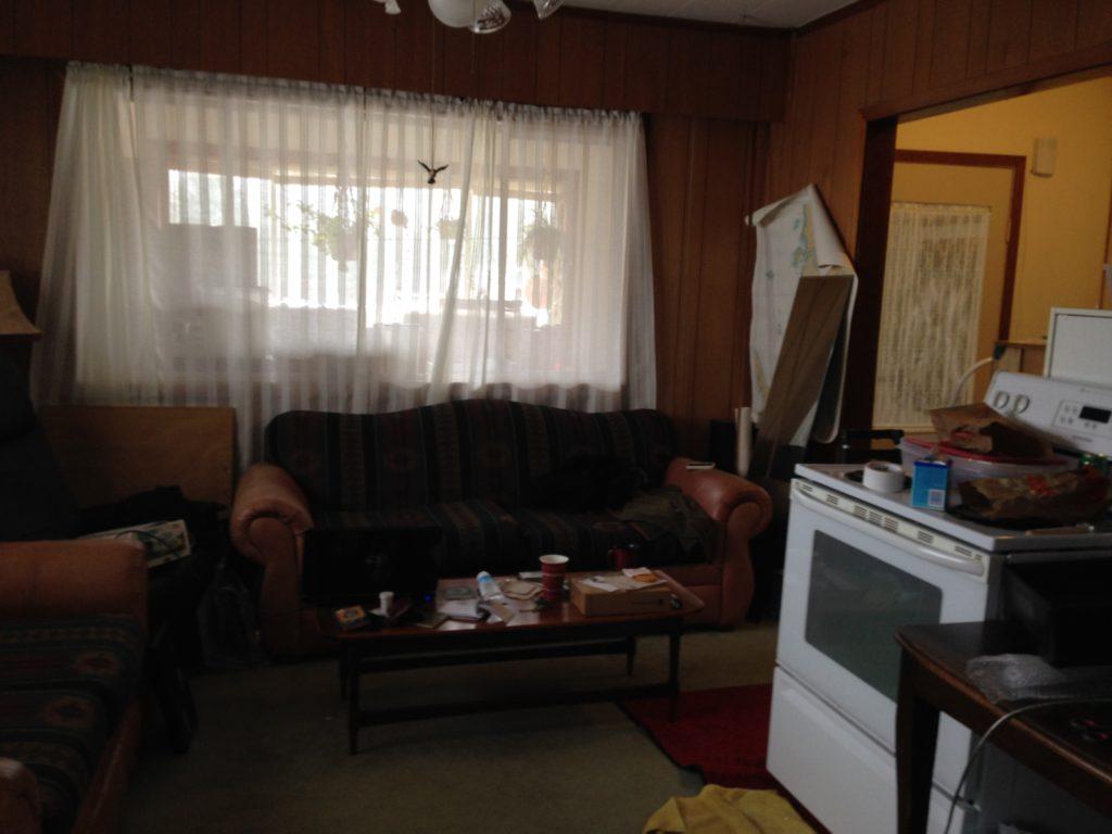Before photo of dark living room before painting paneling.
