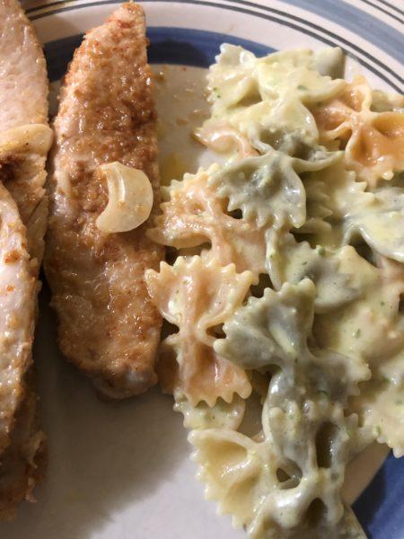 Creamy pesto pasta on a dinner plate alongside grilled chicken.