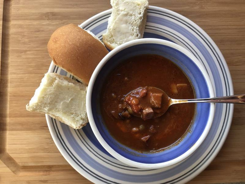 a bowl of warm hearty soup with buttered buns