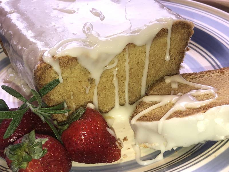 lemon loaf cake with rosemary glaze, on a plate garnished with strawberries.