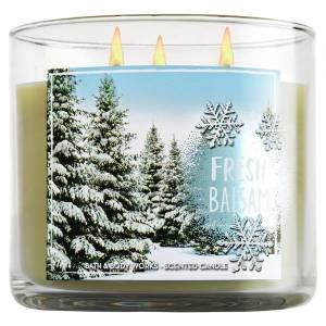 candle with fir trees covered in snow