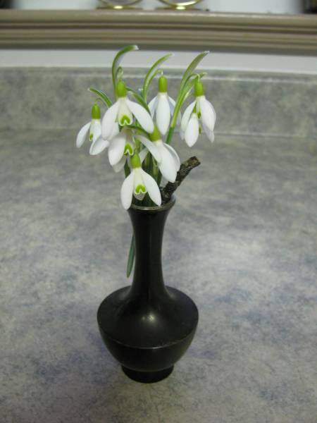 a tiny vase with white snowdrops