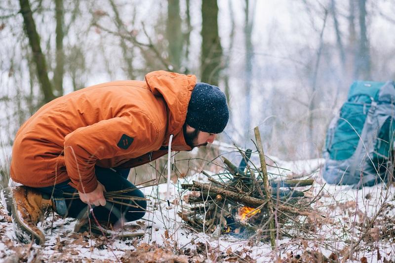 a bundled up man lights a campfire in winter