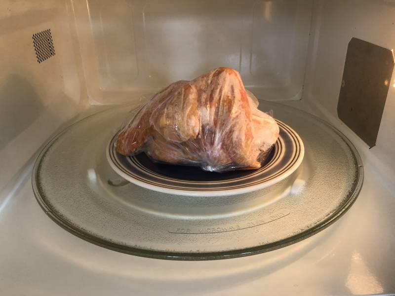 frozen chicken being thawed in microwave