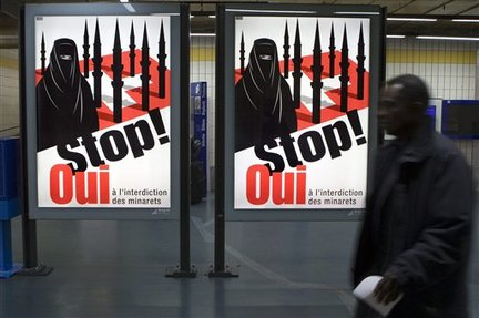 FILE - In this Nov. 4, 2009 file photo a man passes by a poster of the right-wing Swiss People's Party (SVP/UDC) which shows a woman wearing a burqa against a background of a Swiss flag upon which several minarets resemble missiles at the central station in Geneva, Switzerland. An attempt to ban the construction of minarets in Switzerland has set off an emotional debate on Islam in the Alpine nation, stirring fears of boycotts from Muslim countries and of violent reactions. (AP Photo/Keystone, Salvatore Di Nolfi, File)