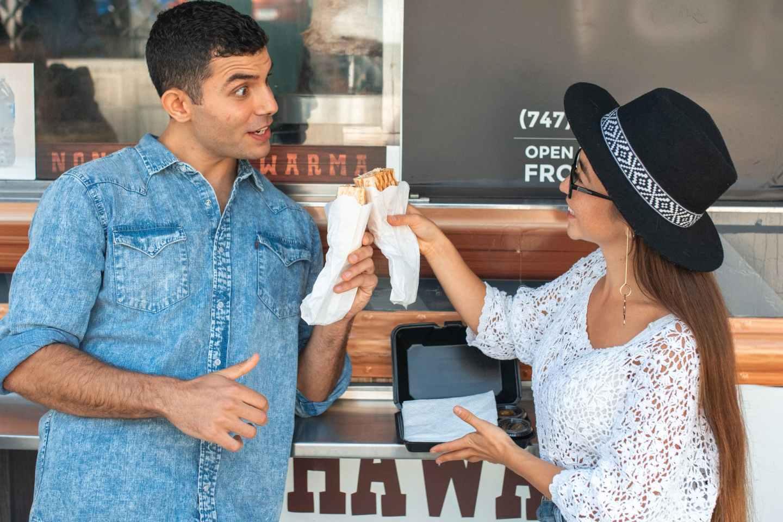 joyful couple clinking sandwiches near food truck