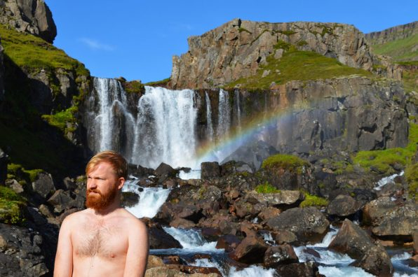 Half naked Daan in front of a waterfall with a rainbow | Gay Couple Road Trip East Iceland © Coupleofmen.com