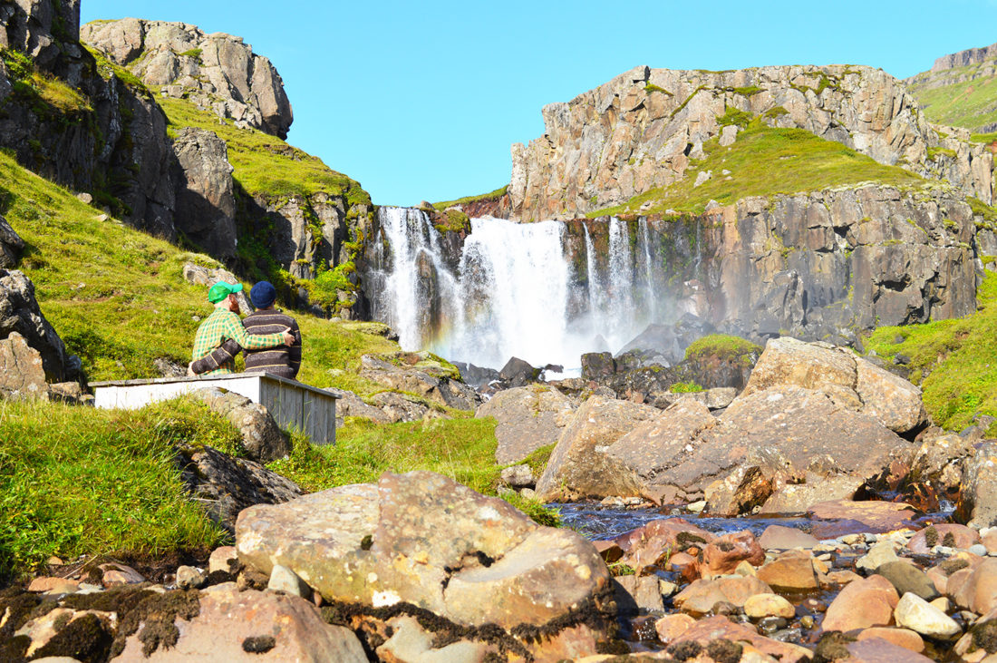 Arm in arm in front of a waterfall | Gay Couple Road Trip East Iceland © Coupleofmen.com