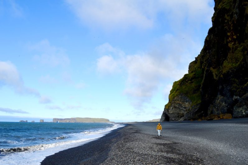 Daan walking along the Black Beaches in South Iceland Vík Black Beach | Gay Couple exploring South Iceland Vík © CoupleofMen.com