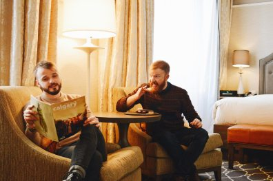 Karl reading about Calgary while Daan secretly eats all sweets | Gay-friendly Fairmont Palliser Hotel Downtown Calgary © CoupleofMen.com