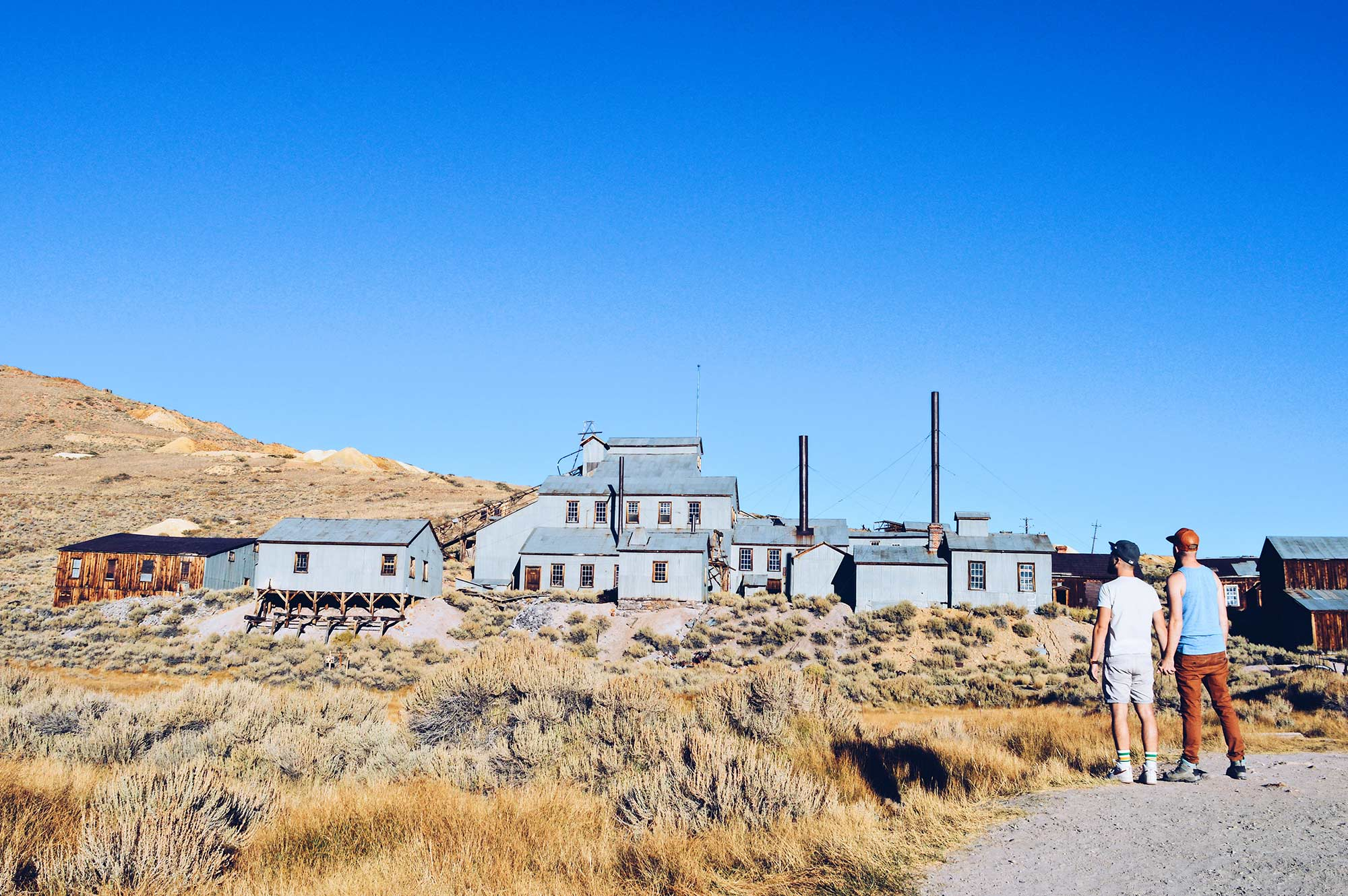 Gay Couple hand in hand gay travel blogger Ghost Town Bodie State Historic Park California © CoupleofMen.com
