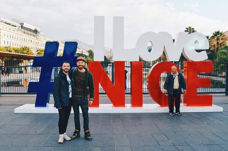 Gay Couple Travel France City Weekend Nice two gay guys in front of the #ILOVENICE sign in the city center of Nice