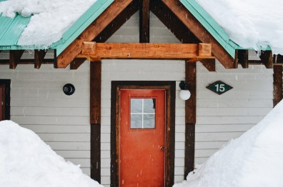 Remarkable red doors & jade-colored roof tops overed with snow | Emerald Lake Lodge gay-friendly © Coupleofmen.com