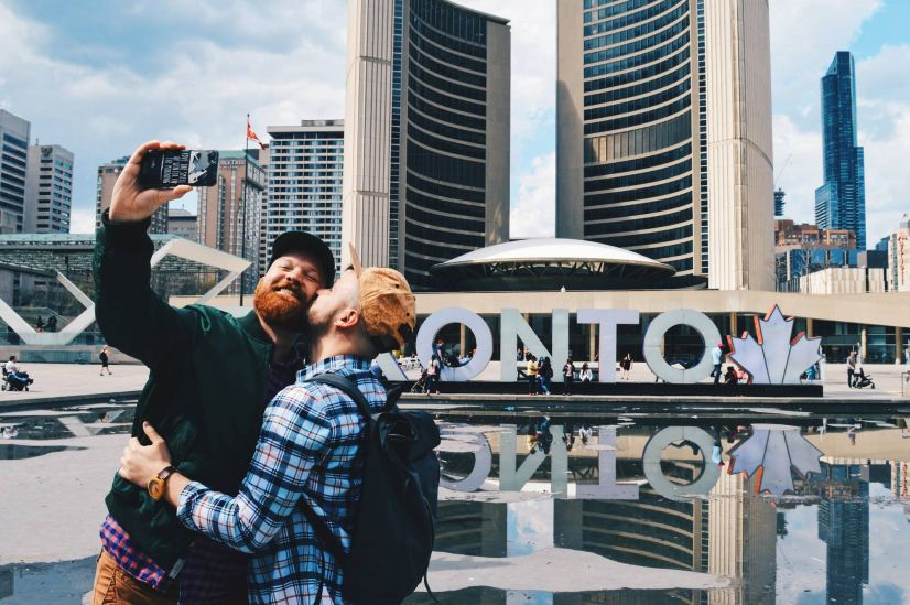 Gay Kiss Selfie infront of the Toronto Sign right next to the Marriott Downtown Toronto Eaton Centre © Coupleofmen.com