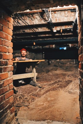 Karl sitting in the historical mass prison cell | Katajanokka Hotel Helsinki Gay-friendly Review © Coupleofmen.com