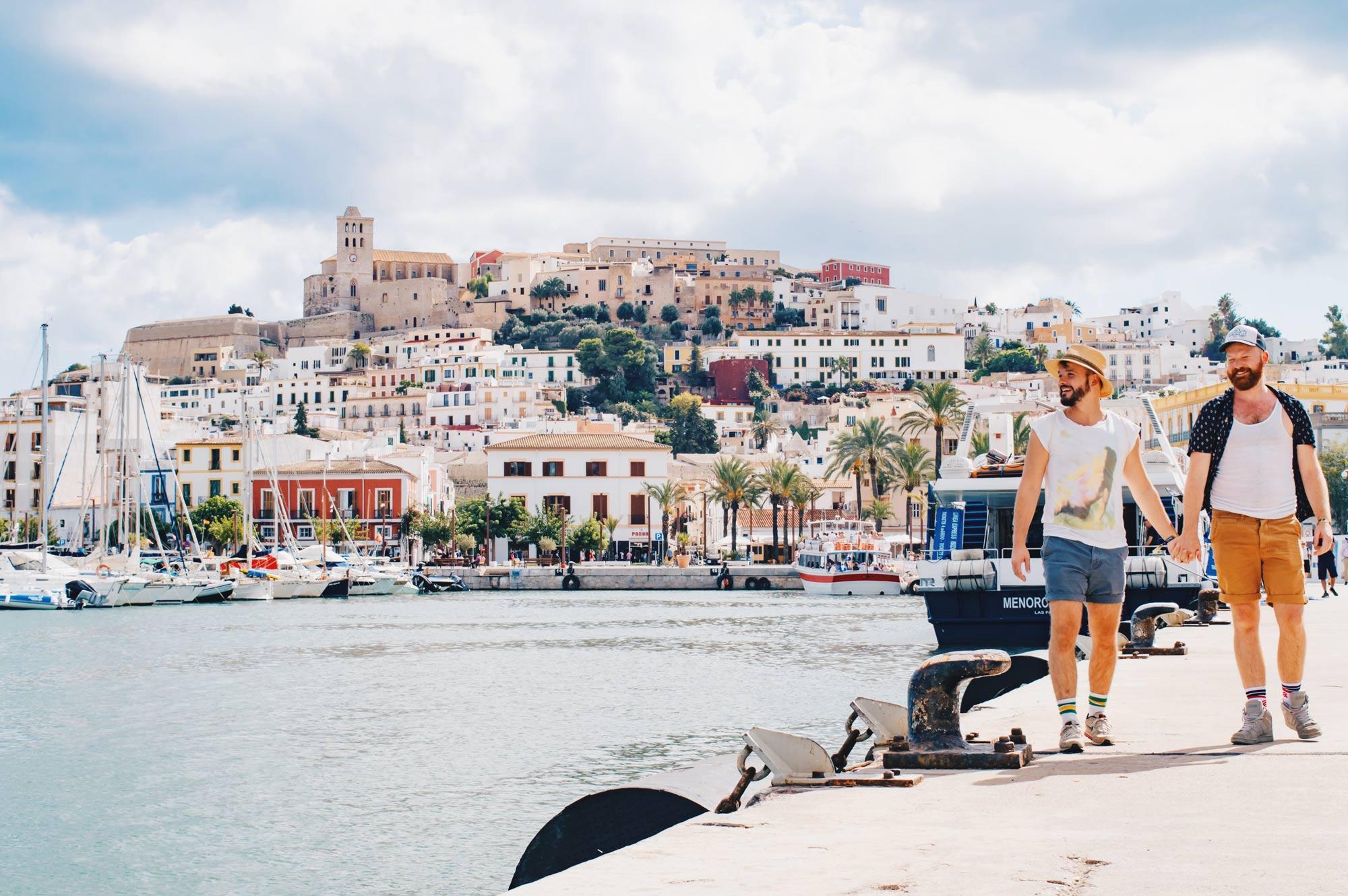 Gay Travel Blogger hand in hand at the Gay Beach in Ibiza | Gay Travel Ibiza © Coupleofmen.com