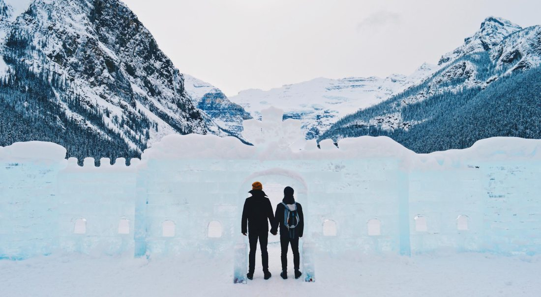 Karl & Daan hand-in-hand in front of the frozen Lake Louise | Winter Road Trip Alberta Highlights Canadian Rocky Mountains © Coupleofmen.com
