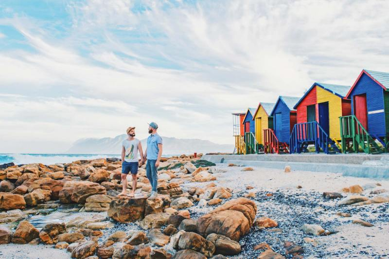 Gay Couple City Trip Cape Town Gay Travel Cape Town: Adventure Days of a Gay Couple standing hand-in-hand in front of colored beach houses in the South of the Mother City © Coupleofmen.com