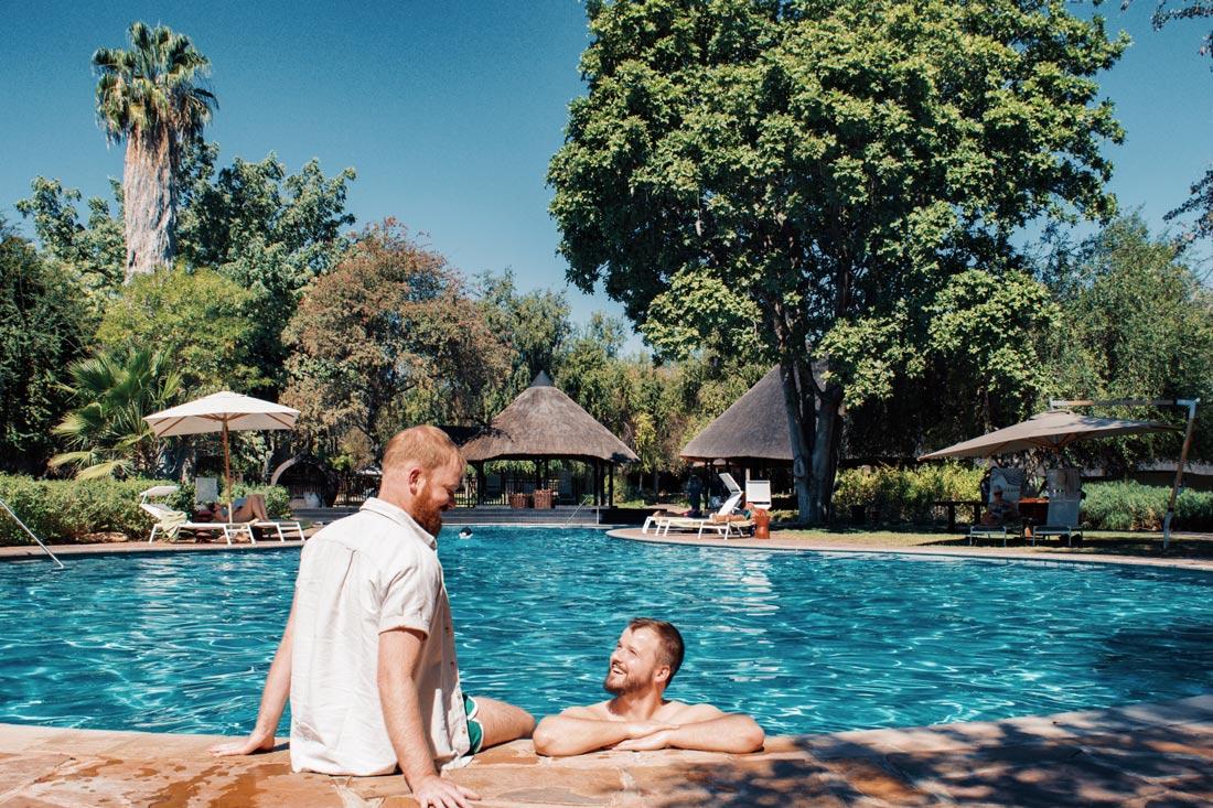 Gay Couple Travel Blogger having a refreshing swim in the pool at Mokuti Lodge at the East Gate of Etosha in Namibia © Coupleofmen.com