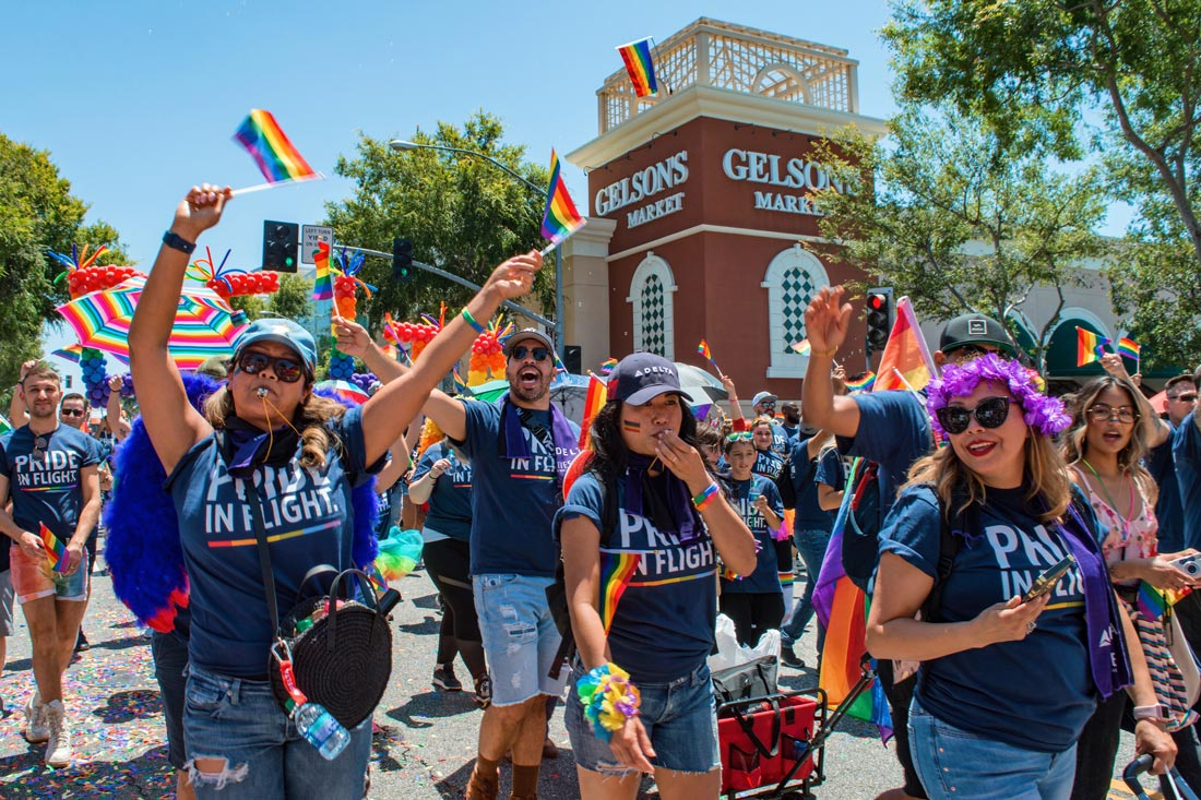 LGBTQ+ and gay-friendly Airline Delta with a huge group of attendees in purple © Coupleofmen.com