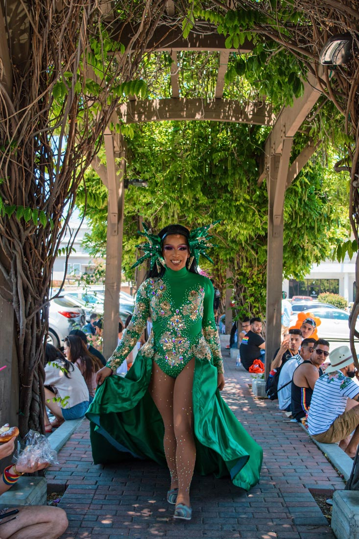 Even during lunch break - Drag Beauty in green dress making a sidewalk to her catwalk © Coupleofmen.com