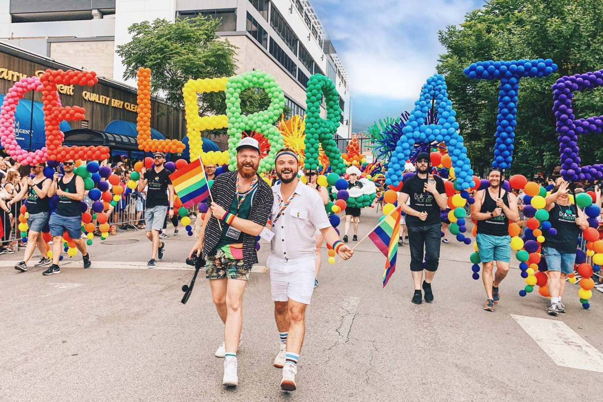 Chicago Gay City Tipps Gay Couple holding hands in front of the Rainbow Balloons Chicago Gay Pride Parade 2019 © Coupleofmen.com