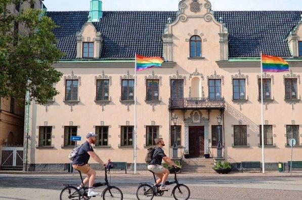 Malmö Gay City Trip South Sweden Biking around Malmö City with Rainbow Flag © Coupleofmen.com
