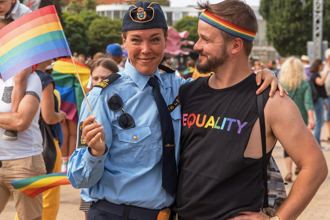 Gay Pride Malmö 2019 Karl posing with a proud police officer protecting the LGBTQ+ festival at Folkets Park Malmö © Coupleofmen.com