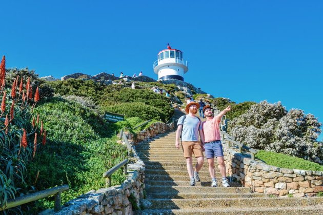 Hand-in-hand on the staircase leading to the red-white Cape Point Lighthouse © Coupleofmen.com