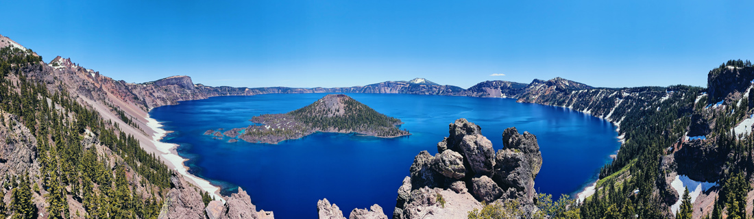 Panorama photo of the deep blue Crater Lake in Oregon in June with summer weather and blue sky © Coupleofmen.com