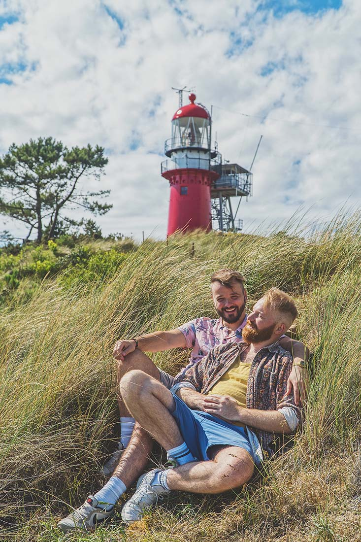"Gay Vlieland Trip Resting in front of Vlieland's landmark ""Vuurtoren"" - lighthouse © Coupleofmen.com"