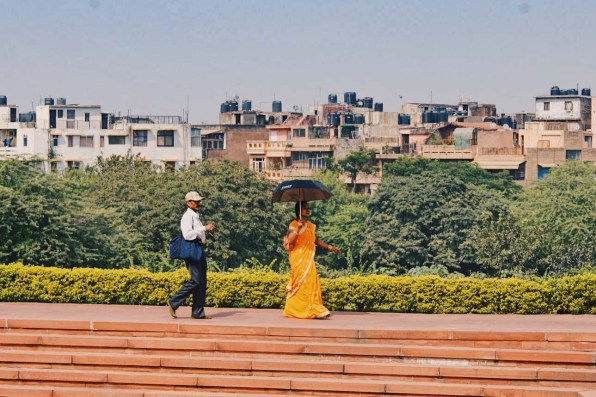 Lotus Temple in New Delhi and an orange dressed woman with black umbrella © Coupleofmen.com