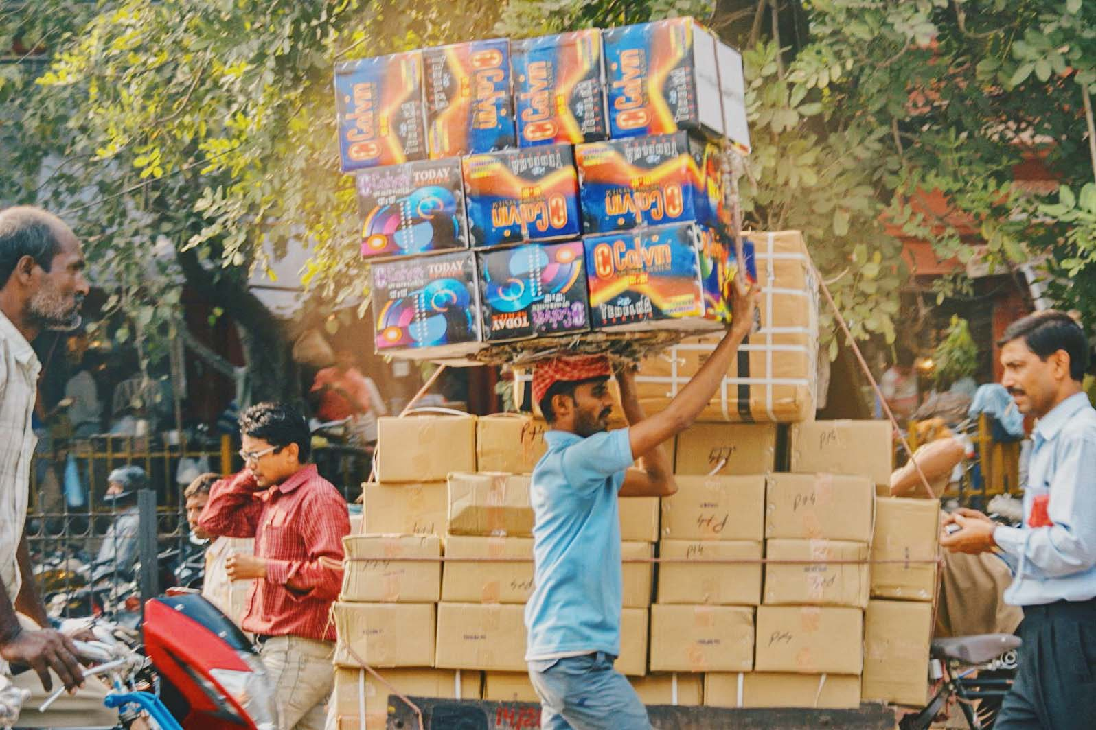 Gay Reise Indien Streetlife in New Delhi with a man carrying boxes on his head © Coupleofmen.com