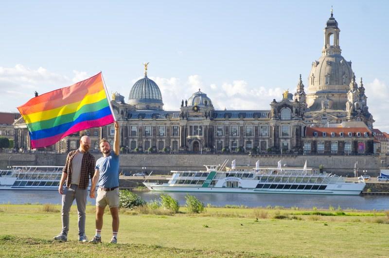 Dresden Gay City Trip Couple of Men with a rainbow flag in front of the Panorama-Dresden Altstadt © Coupleofmen.com