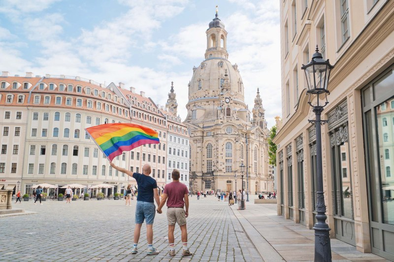Dresden Gay City Trip: Gay Couple waving a rainbow flag in front of the Church of Our Lady (German: Frauenkirche) © Coupleofmen.com