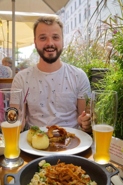Munich Gay City Trip Karl happily enjoying his lunch with a good beer © Coupleofmen.com
