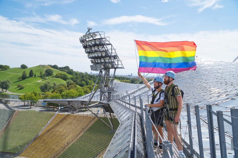 Munich Gay City Trip Proudly waving the rainbow flag as a gay couple on the rooftop of the Olympic Stadium from 1972 © Coupleofmen.com