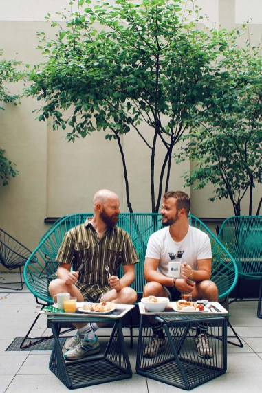 The gay couple enjoying breakfast outside in the inner courtyard of the LGBTQ+ friendly accommodation in Munich © Coupleofmen.com