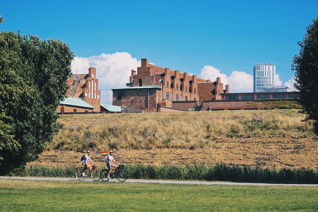 Biking around Malmö parks with the Malmö Castle in the background © Coupleofmen.com