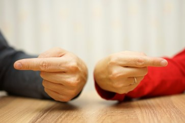 adult couple has difficulties in relationship an both shows the finger at himself and herself