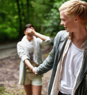 A girl covering her eyes with her hand is led through the forest by her boyfriend