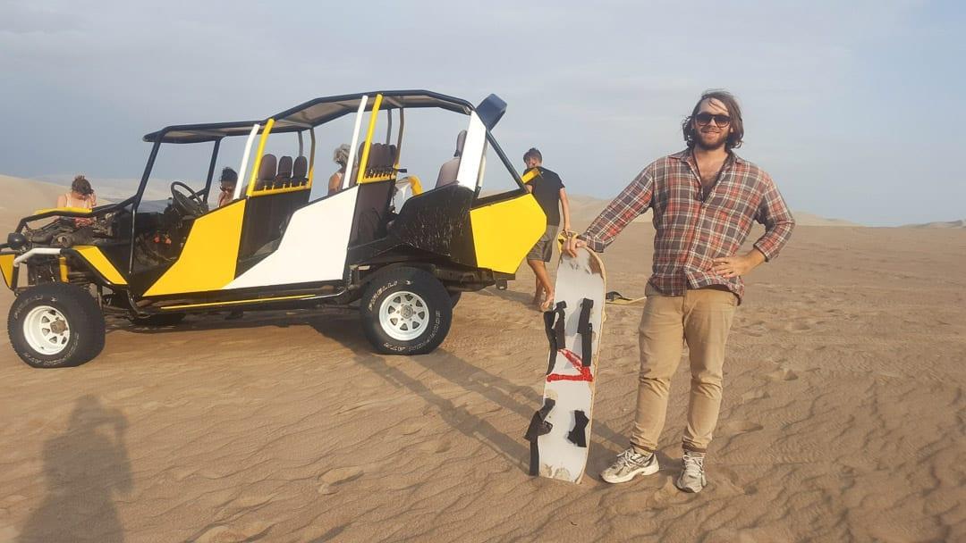 man-standing-with-sandboard-on-huacachina-tour