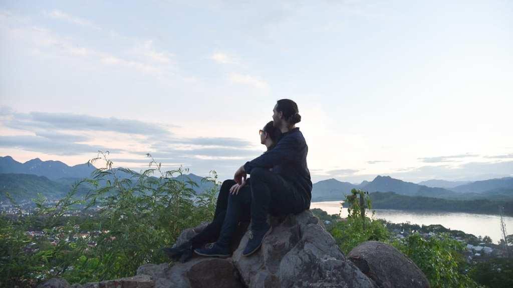 A travel couple watching sunset at Mount Phousi, Laos