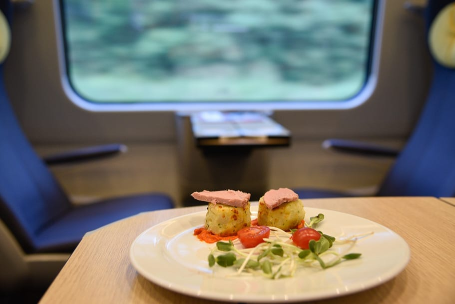Duck meal on the table of the 1st class carriage with scenery behind on the train from Krakow to Gdansk