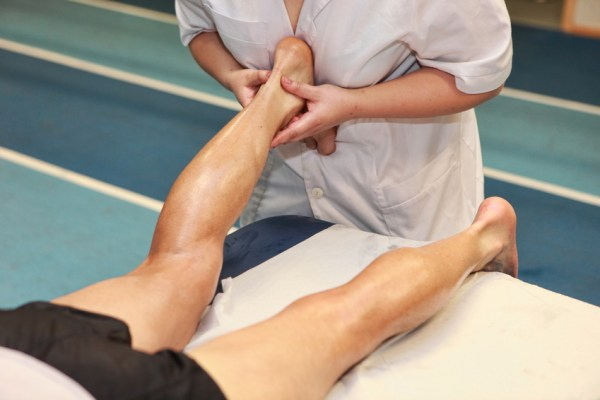 masseuse massaging athlete' s Achilles tendon after running