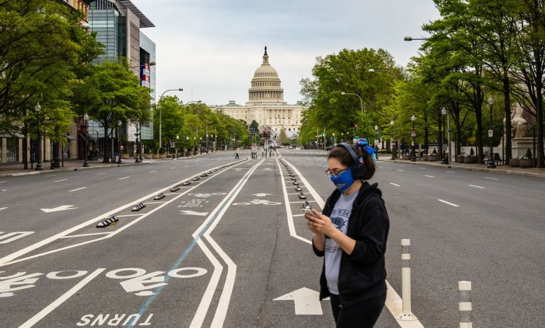Une jeune femme masquée passant devant le capitole des Etats-Unis, à Washington DC.