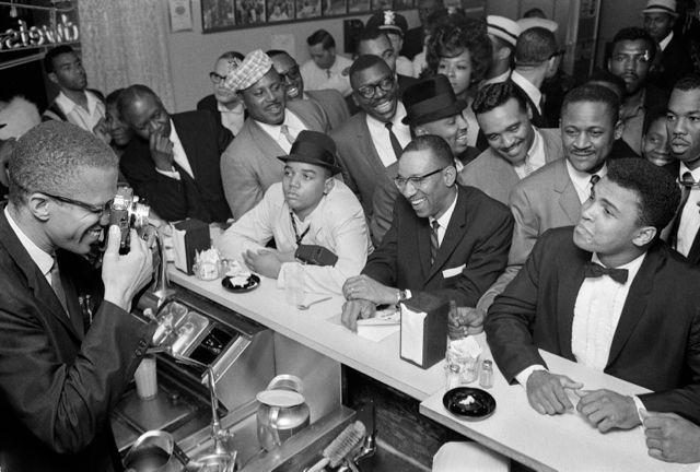 """La """"vraie"""" soirée de victoire : Malcom X prenant Cassius Clay en photo. Copyright Bob Gomel Crédit photo : EPHouston - Own work, CC BY-SA 4.0"""