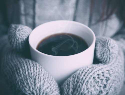 peaceful hands wearing mittens and holding a hot cup of coffee.